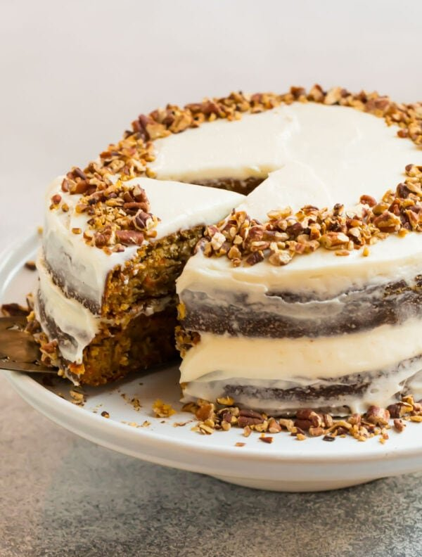 An almond flour gluten free carrot cake with cream cheese frosting and chopped nuts