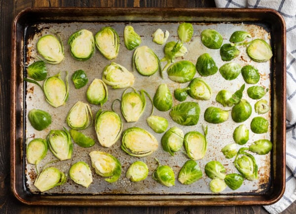 Sliced brussels sprouts on a sheet pan ready to be roasted for Brussels sprouts chips