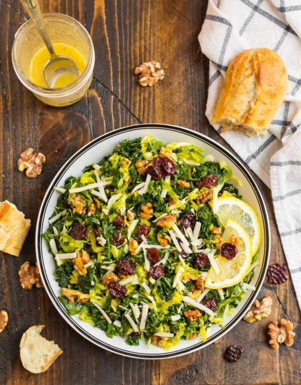 Kale Brussel Sprout Salad with Walnuts and Parmesan in a white bowl