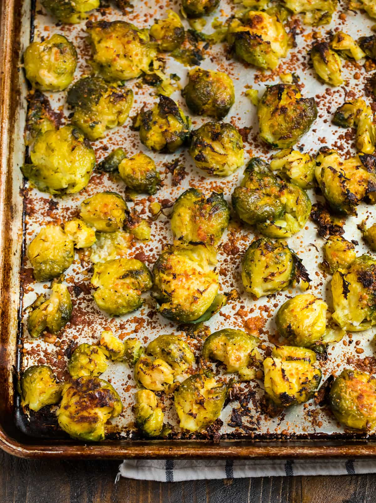 Crispy smashed Brussels sprouts on a baking sheet with Parmesan