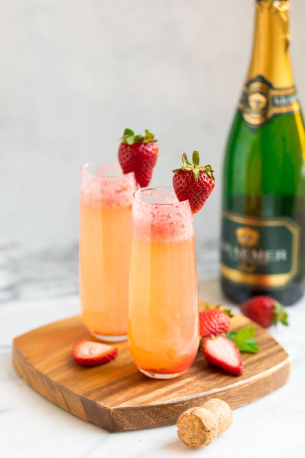 Two champagne glasses filled with a strawberry and champagne cocktail