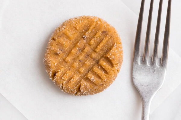 a fork beside an unbaked peanut butter cookie