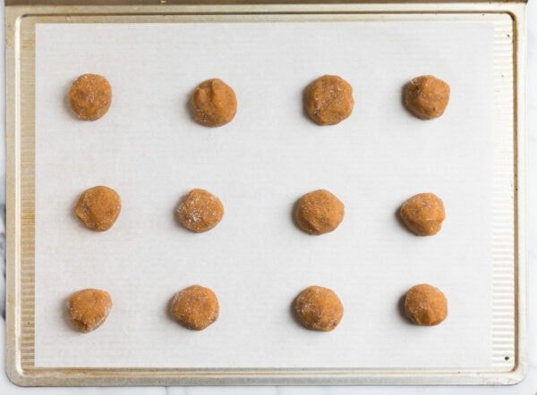 a cookie sheet with balls of peanut butter cookie dough rolled in sugar