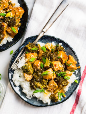A plate with slow cooked chicken and steamed broccoli florets in an Asian ginger sauce