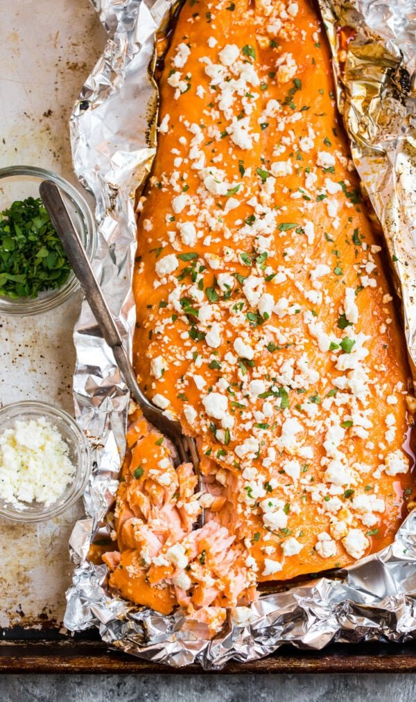 baked salmon with Franks hot sauce being flaked with a fork