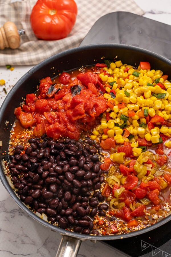 A skillet with black beans, tomatoes, quinoa, and onions