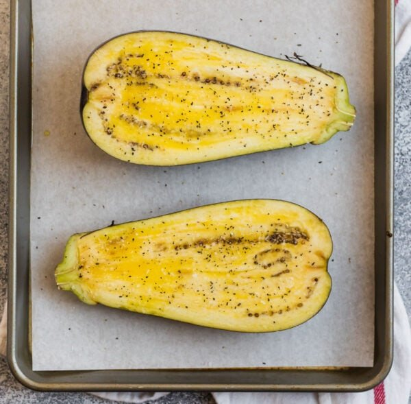 An eggplant split in half on a sheet pan with olive oil, salt, and pepper