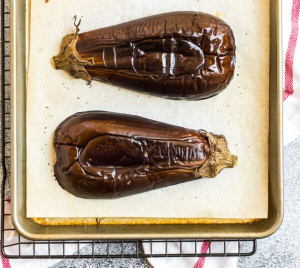 A sheet pan with two tender roasted eggplant halves