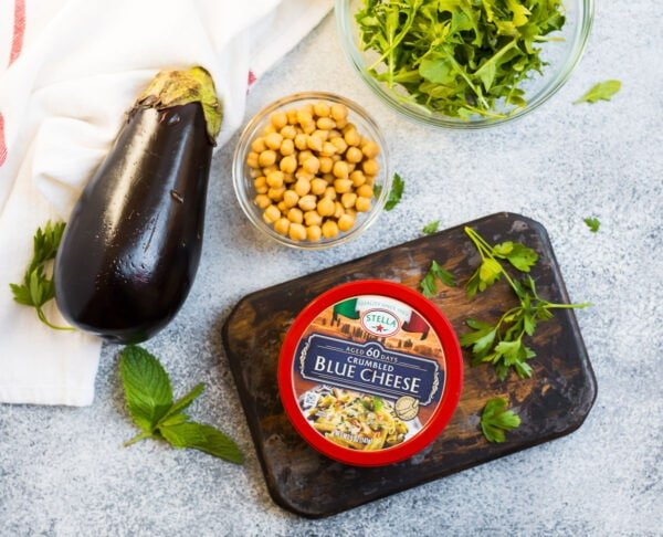 A container of Stella crumbled blue cheese, an eggplant, a bowl of chickpeas and arugula