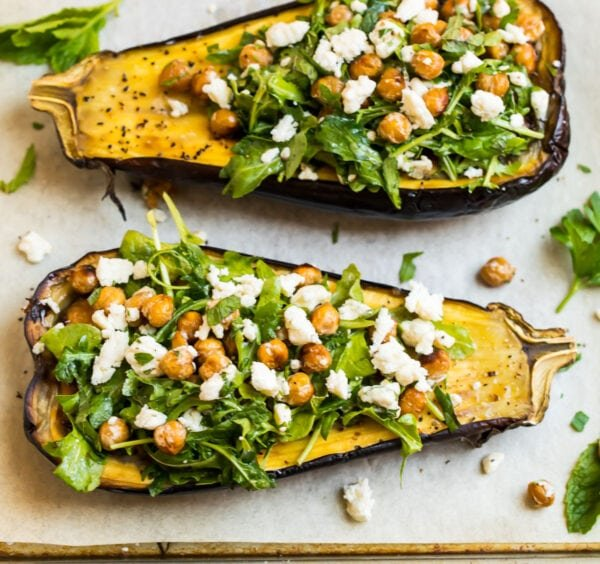two roasted eggplant halves topped with a crispy chickpea arugula salad and blue cheese