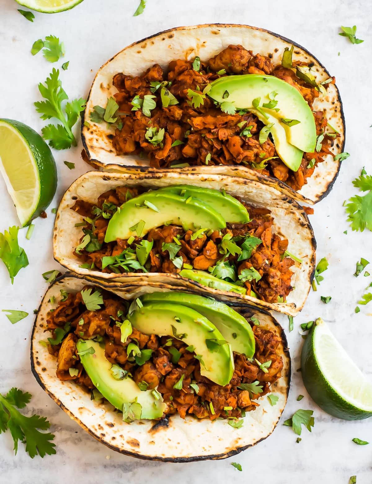 sweet potato tempeh tacos topped with avocado slices