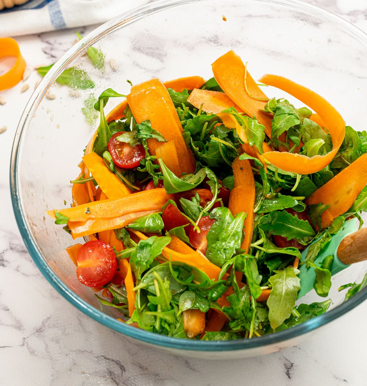Arugula, shaved carrots, and tomatoes in a bowl