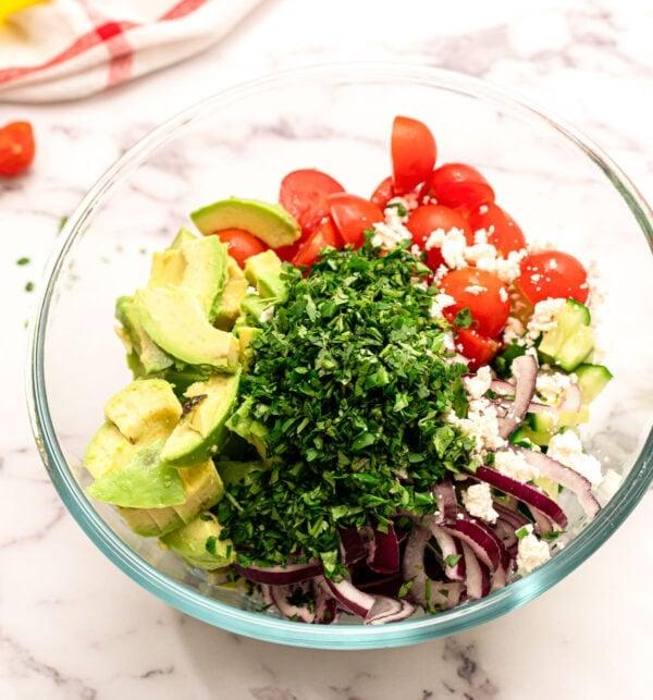 Avocat, tomate, oignon rouge, concombre et herbes dans un bol