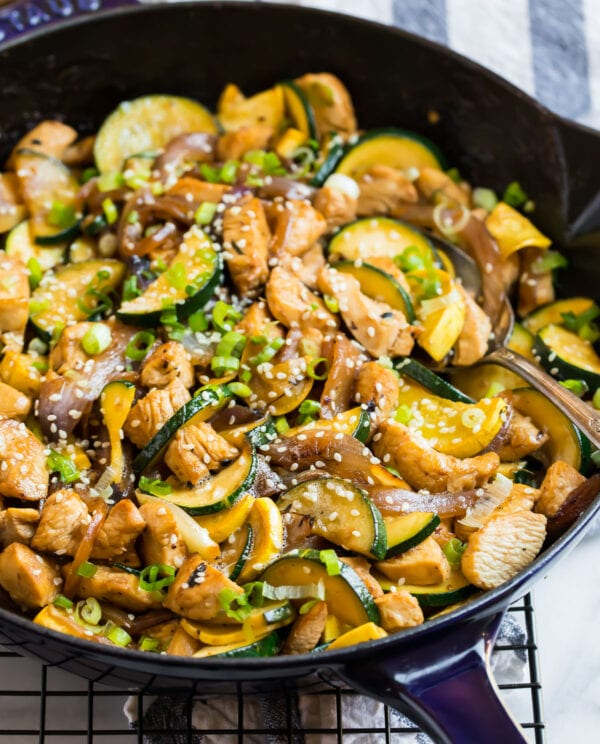 Chicken zucchini stir fry with sesame seeds in a skillet