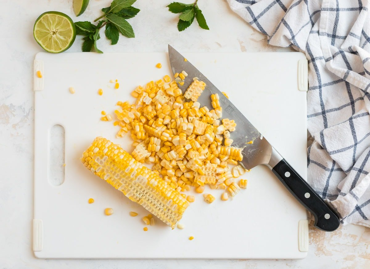 Corn being cut off the cob on a cutting board