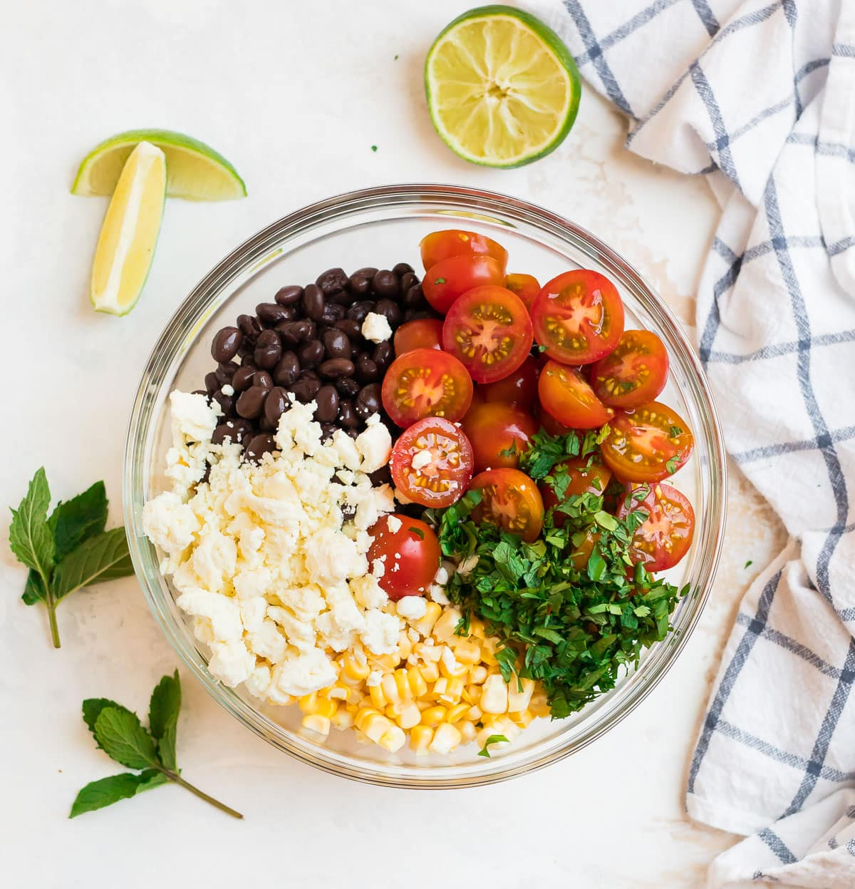 Feta, black beans, tomatoes, herbs, and corn in a bowl