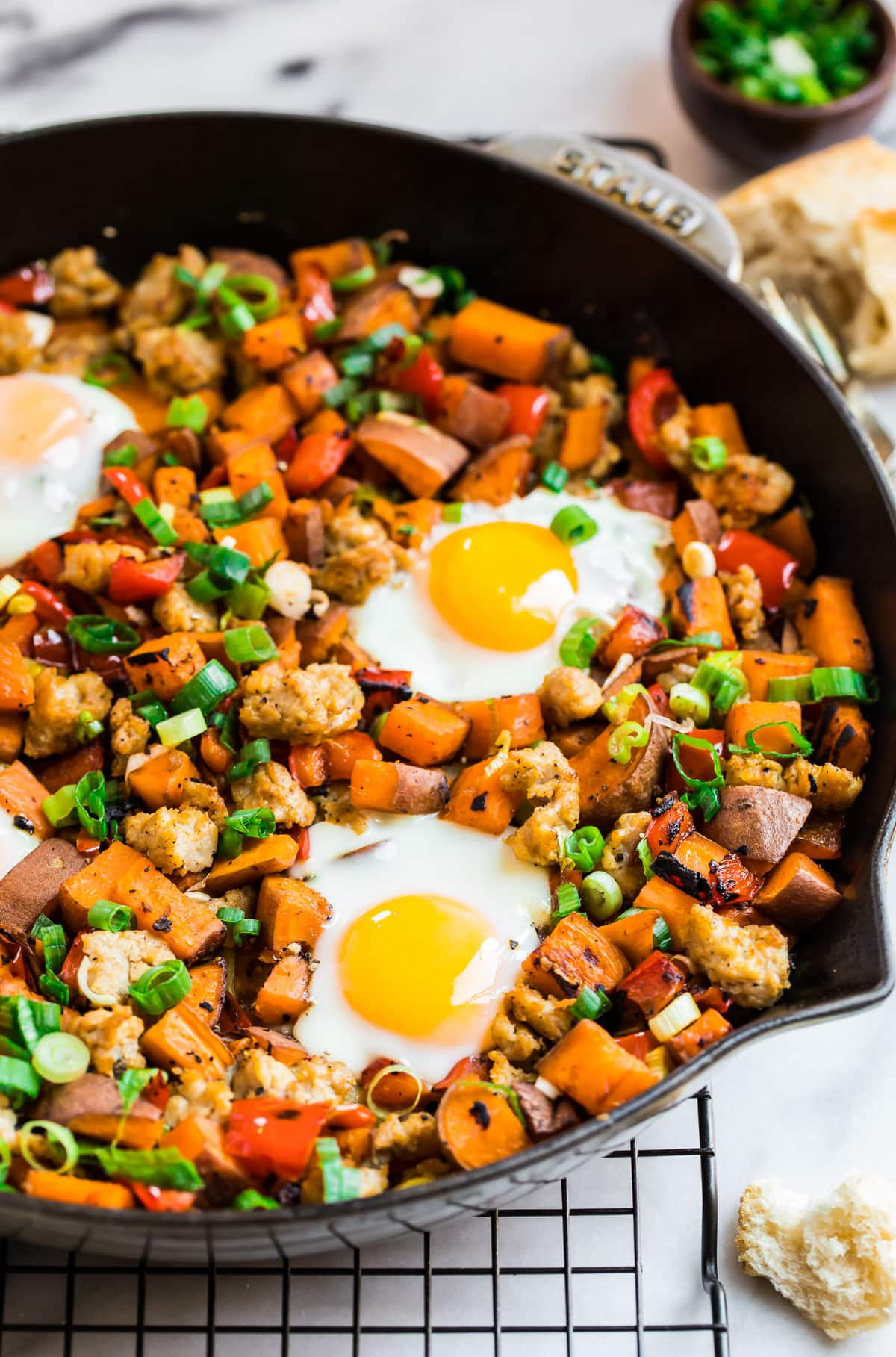 eggs baked on top of sweet potato hash with sausage and red bell peppers