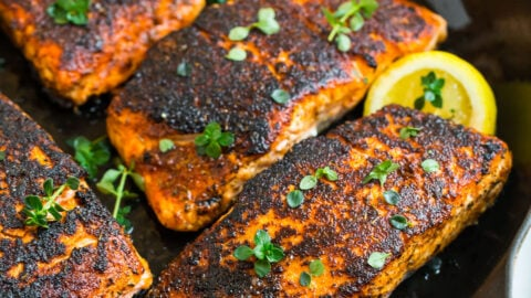 Four blackened salmon filets in a skillet