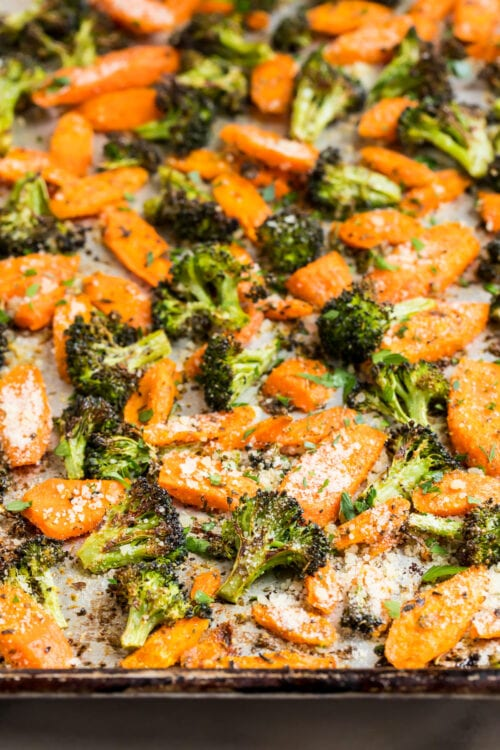Parmesan roasted broccoli and carrots on a baking sheet