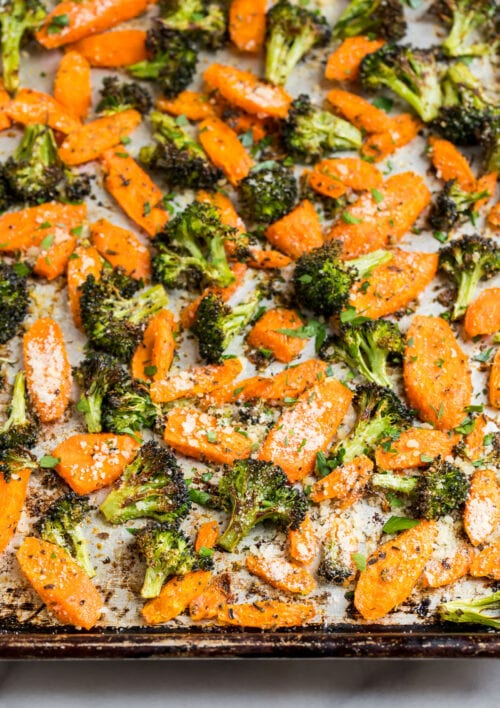 Roasted broccoli and carrots on a baking sheet with Parmesan