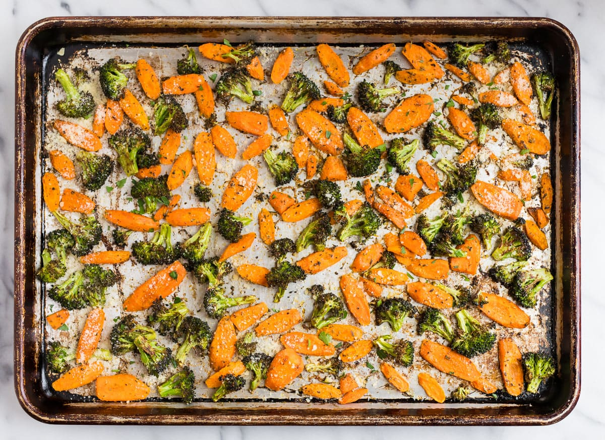 Healthy roasted carrots and broccoli on a baking sheet