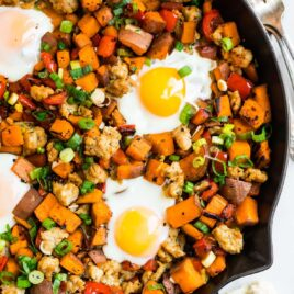 a skillet with sweet potato and sausage hash with peppers and eggs
