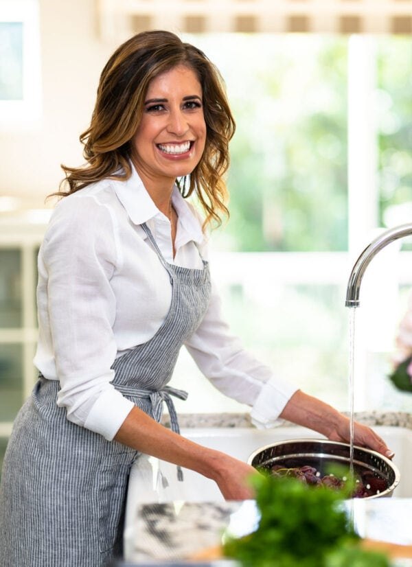 Erin Clarke, cookbook author and healthy food blogger, washing grapes at a sink