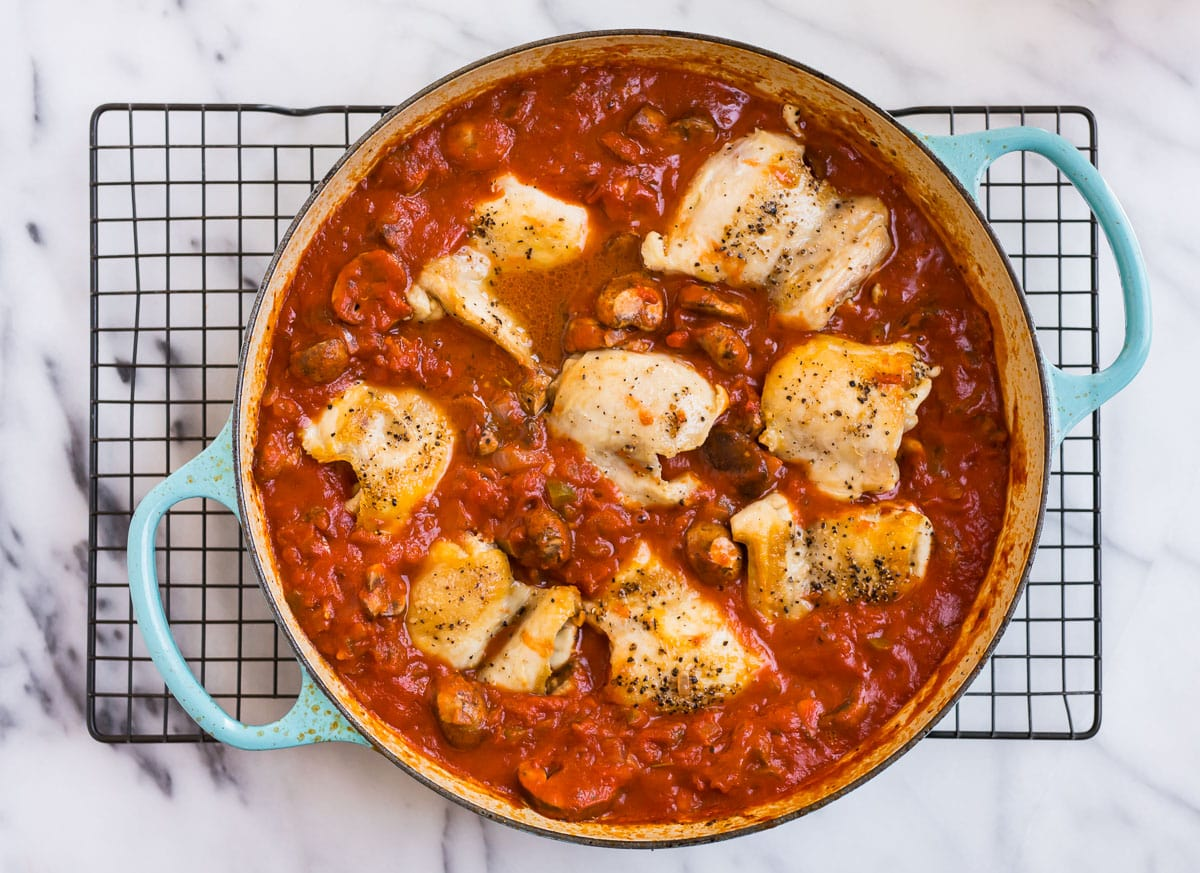 Chicken thighs in a red sauce in a Dutch oven