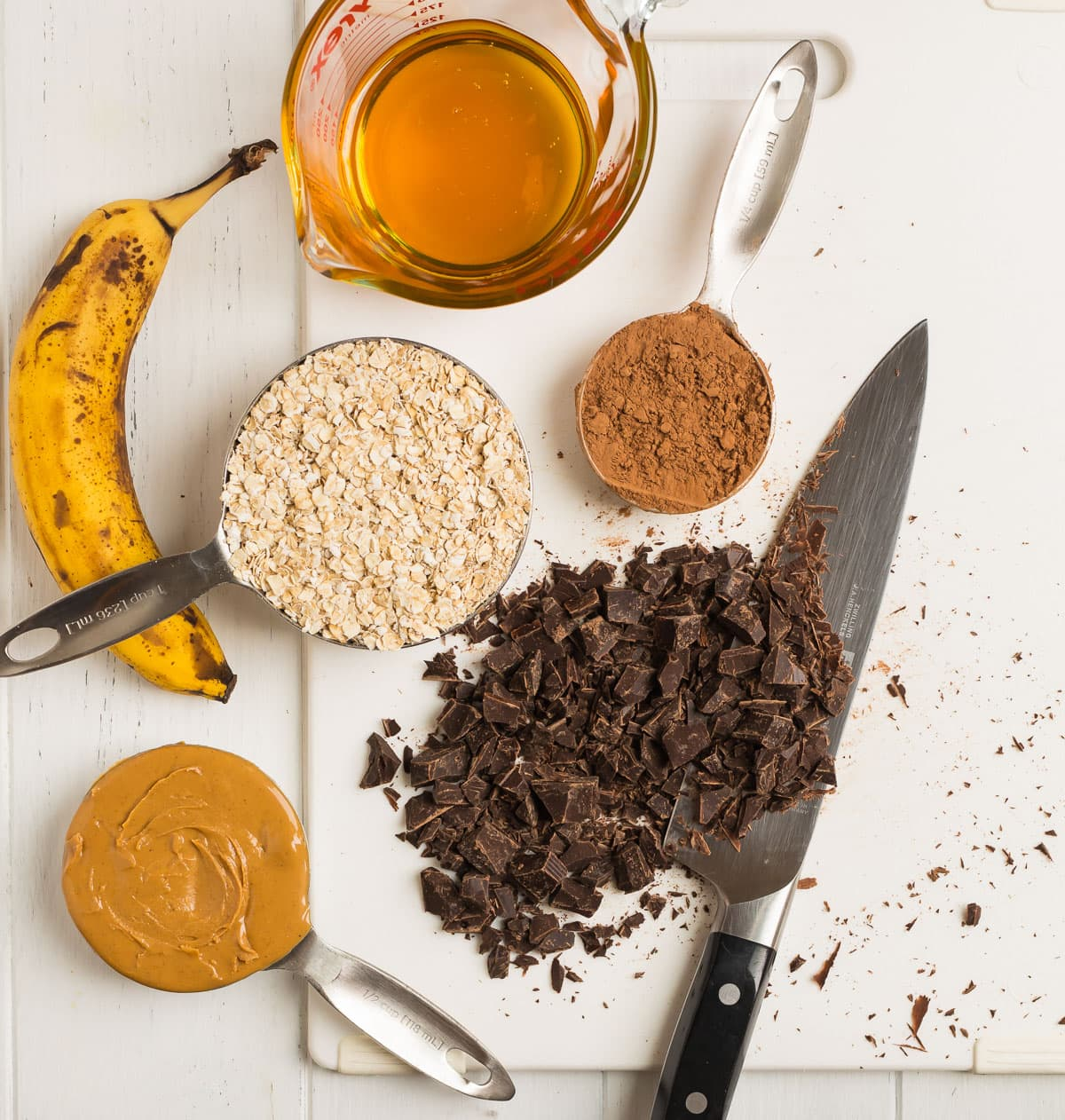 ingredients for making no bake cookies including oatmeal, honey, banana, and chocolate