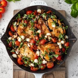 A white skillet with Caprese Chicken
