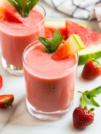 Two glasses of a creamy watermelon smoothie with strawberry and mint