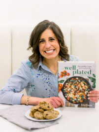 Erin Clarke holding the Well Plated Cookbook with a plate of chocolate chip cookies