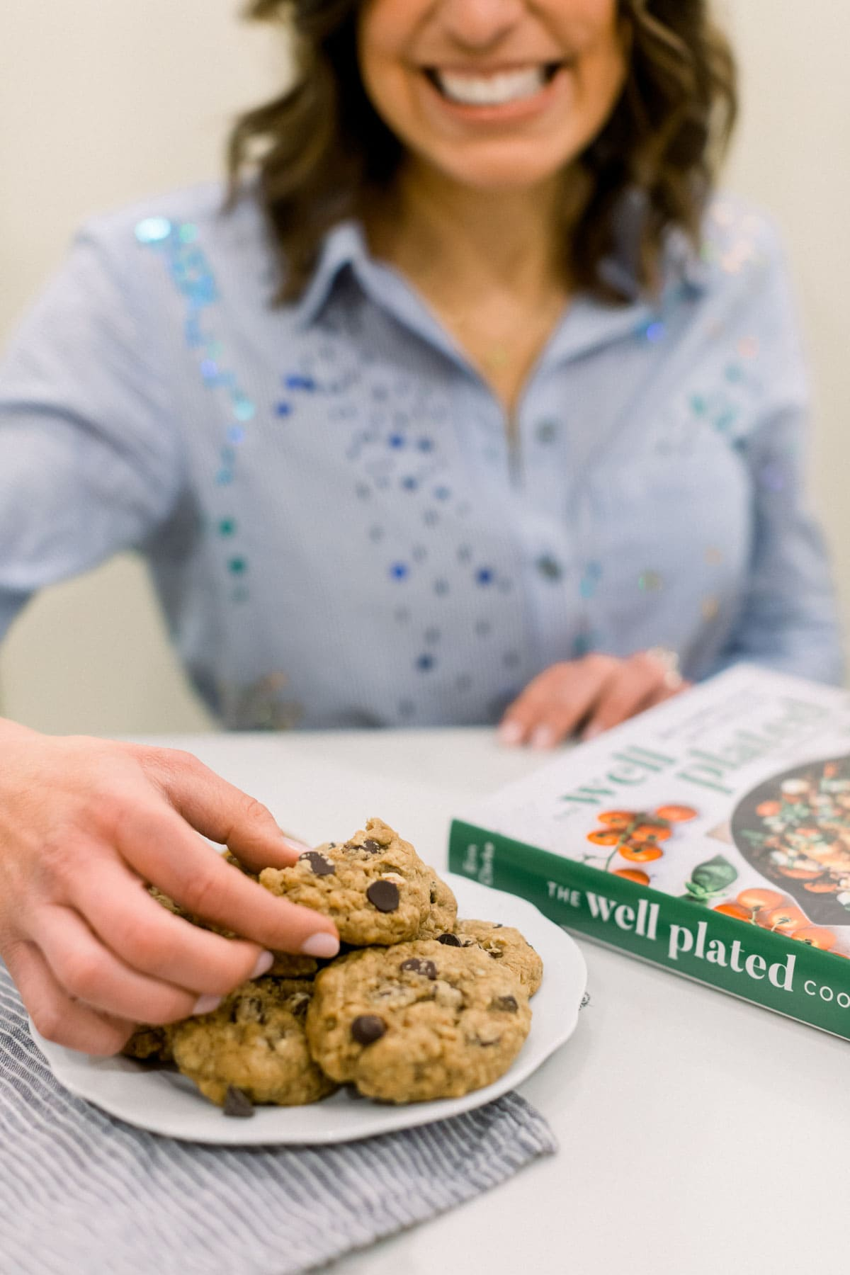 Erin Clarke holding a cookie next to a copy of her cookbook