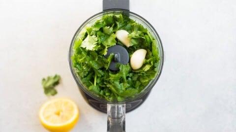 Cilantro, garlic, and lemon juice in a food processor