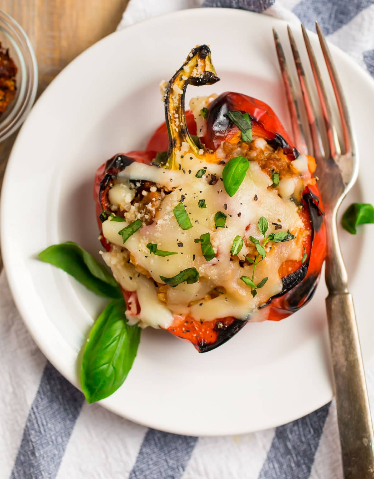 A grilled stuffed pepper with cheese on a white plate