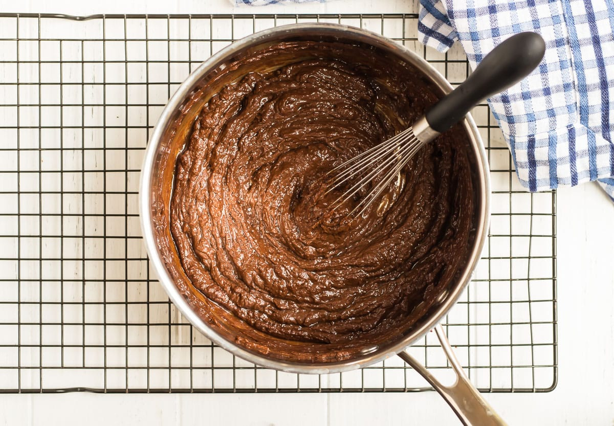 A pot with a mixture of chocolate, peanut butter, and honey no bake cookie batter