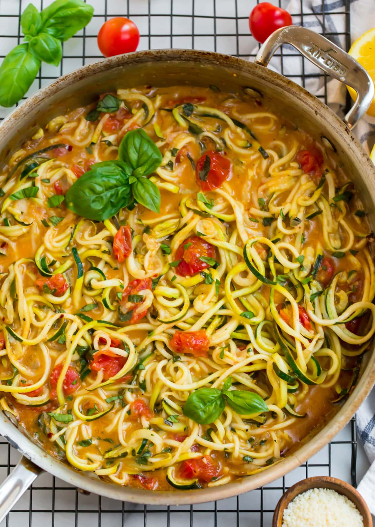 Healthy zucchini pasta in a skillet with tomatoes and basil