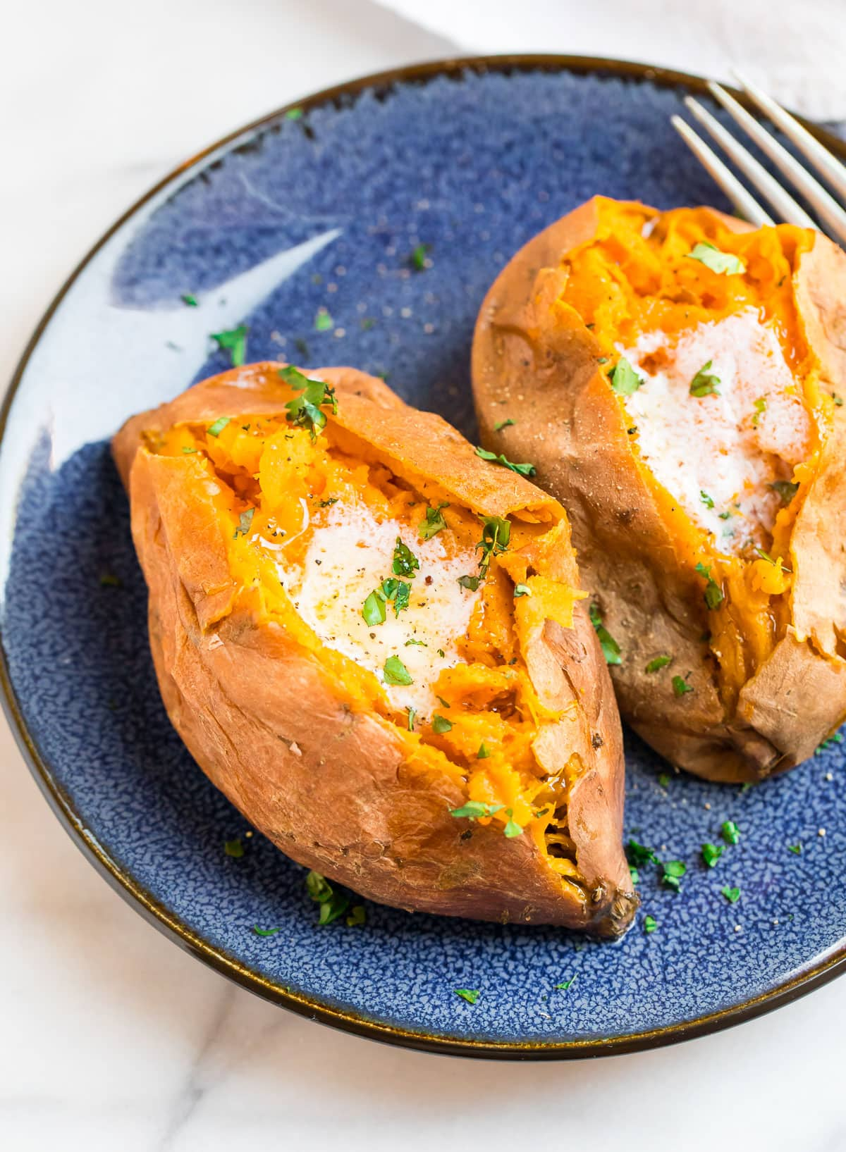 Sweet potatoes with melted butter on a blue plate