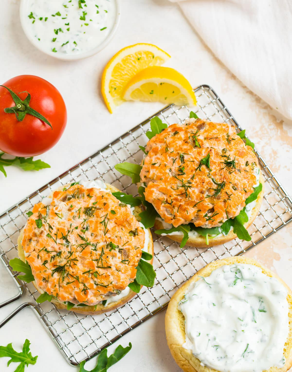 Two salmon burgers on buns with sauce