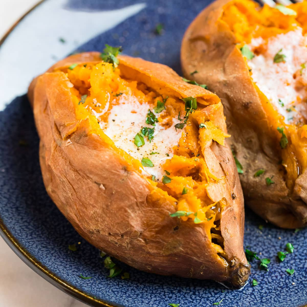 A sweet potato that's been cut open and served with butter