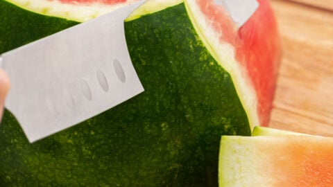 A watermelon being sliced with a knife