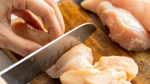 Chicken being sliced on a cutting board