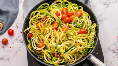 Zucchini pasta in a skillet with tomatoes