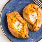 Two sweet potatoes with butter on a blue plate