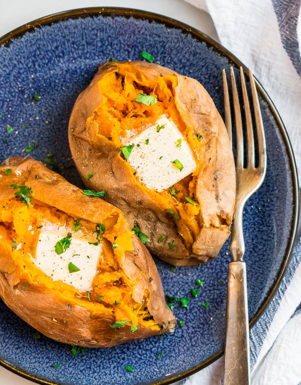 Sweet potatoes served on a blue plate with butter