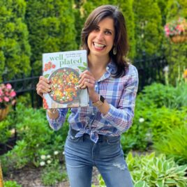 Erin Clarke holding finished copy of The Well Plated Cookbook