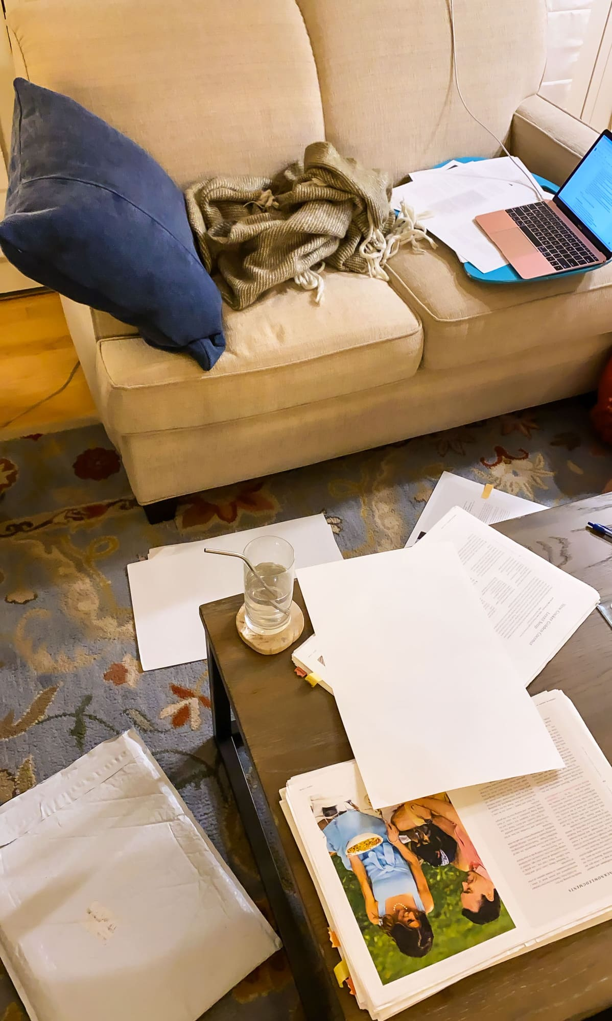 Couch covered in papers with a laptop