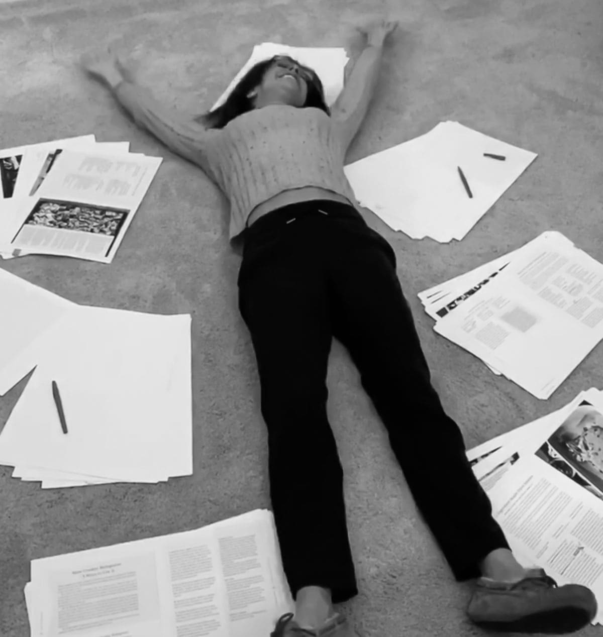 Girl on floor surrounded by papers
