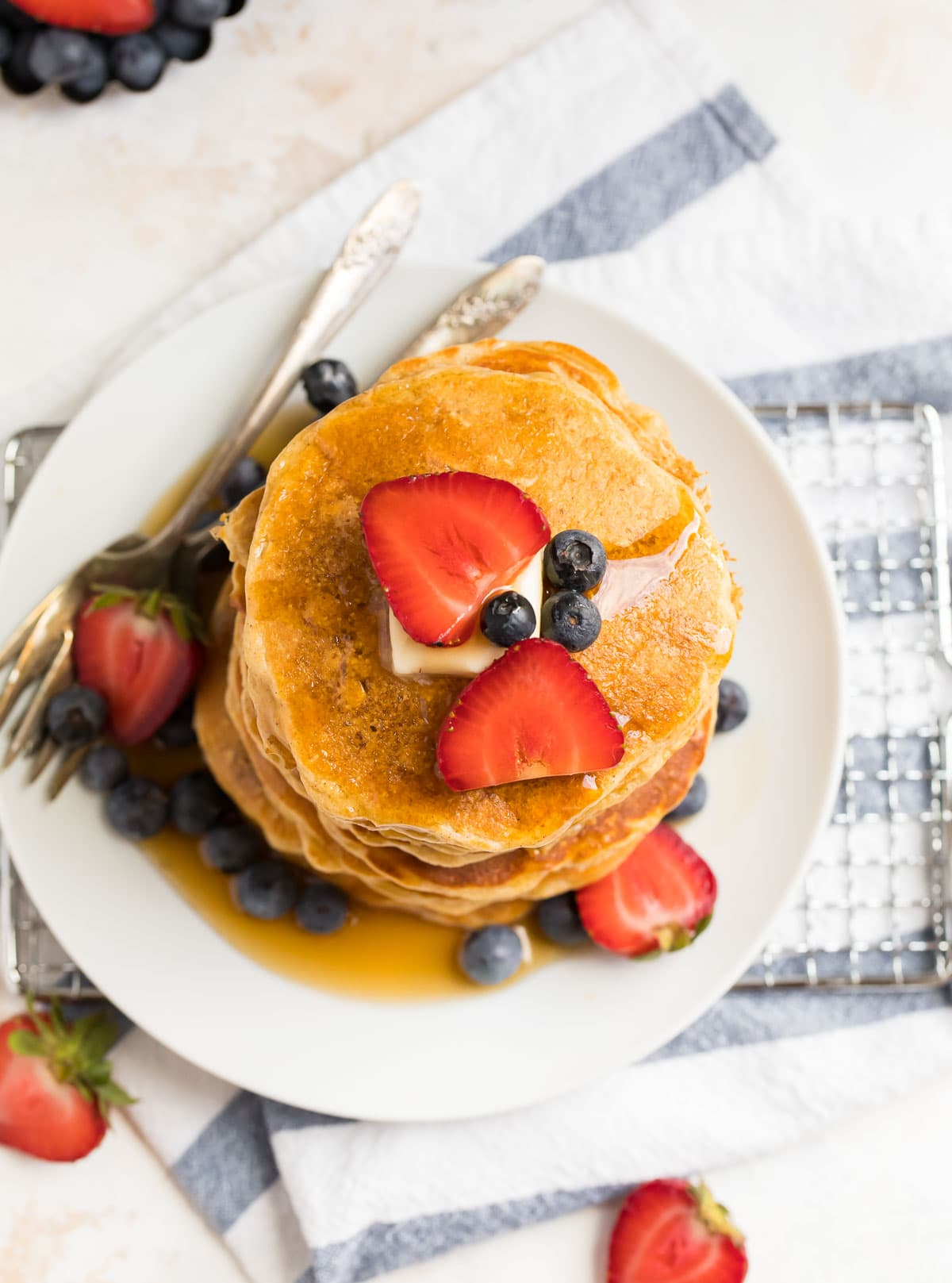 Oatmeal pancakes with berries, butter, and syrup