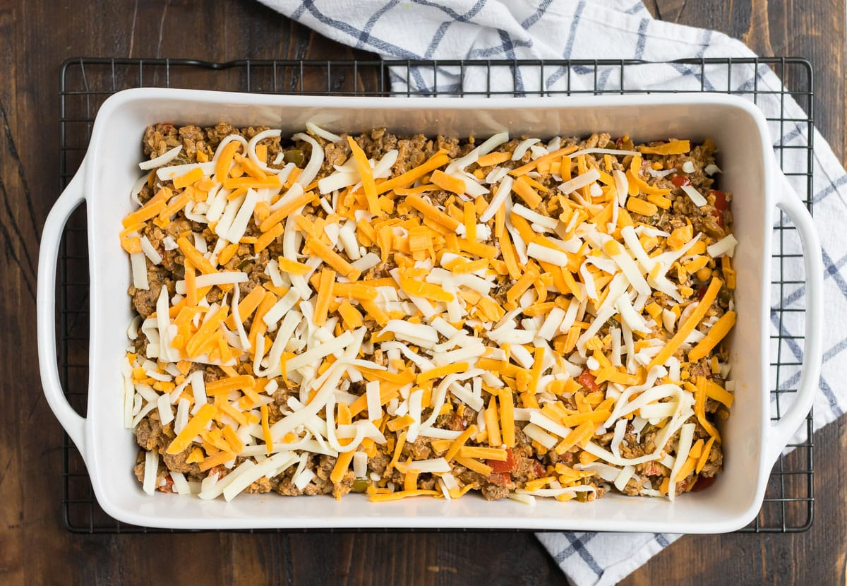 Shredded cheese on ground meat in a baking dish